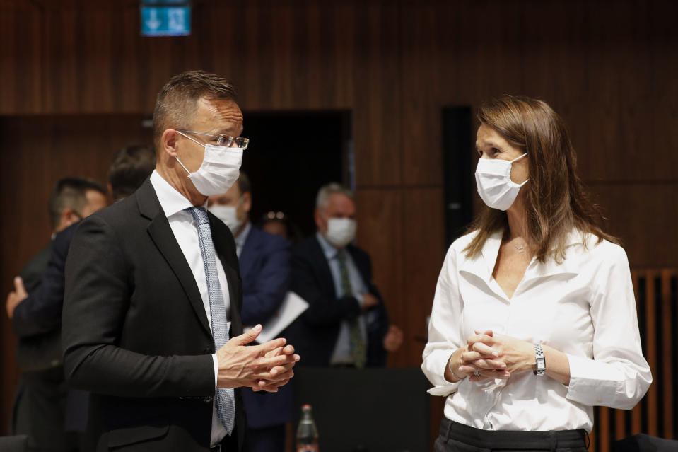 Belgium's Foreign Minister Sophie Wilmes, right, talks to her Hungarian counterpart Peter Szijjarto during a European Foreign Affairs Ministers meeting at the European Council building in Luxembourg, Monday, June 21, 2021. EU foreign ministers were set to approve Monday a new set of sanctions against scores of officials in Belarus and prepare a series of measures aimed at the country's economy. (Johanna Geron/Pool Photo via AP)