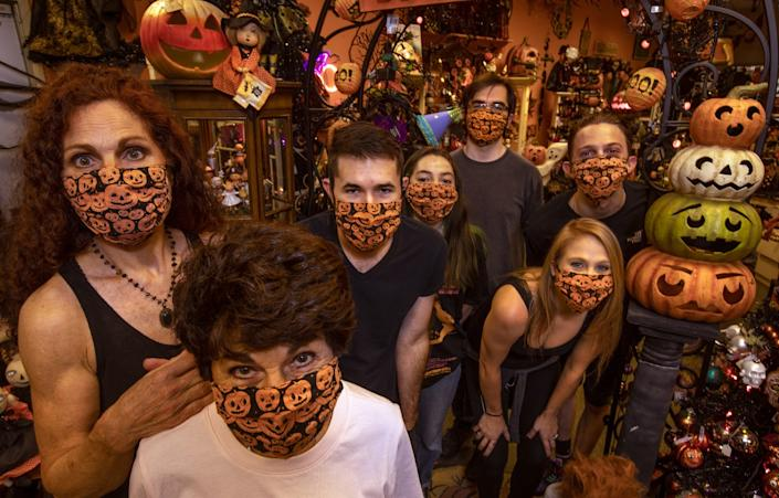 "The staff at Traditions, a holiday decor shop in Canoga Park, gather to show off their popular new product: Halloween-themed face masks. At left is owner Debi Thomas, standing behind her mohter, Barbara: The pair started the business 27 years ago. <span class=""copyright"">(Mel Melcon / Los Angeles Times)</span>"