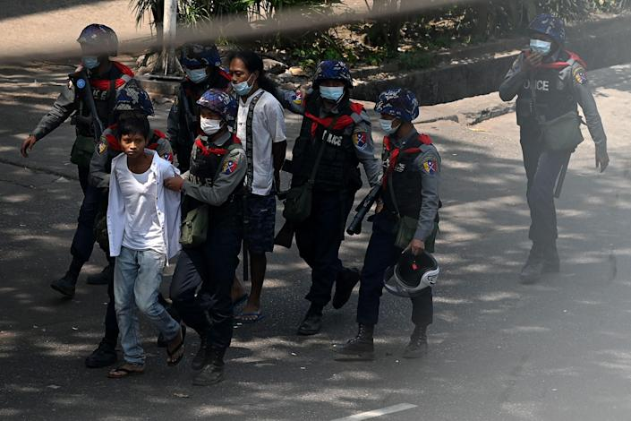 <p>Police arrest people in Yangon on 27 February as protesters demonstrate against country's military coup</p> (AFP via Getty Images)