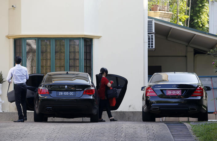 Unidentified persons get out of a car at the North Korean Embassy in Kuala Lumpur, Malaysia, Saturday, March 20, 2021. Malaysia said Friday it will order all North Korean diplomats to leave the country within 48 hours, an escalation of diplomat brawl over Malaysia's move to extradite a North Korean suspect to the United States for money laundering charges. (AP Photo/Lai Seng Sin)