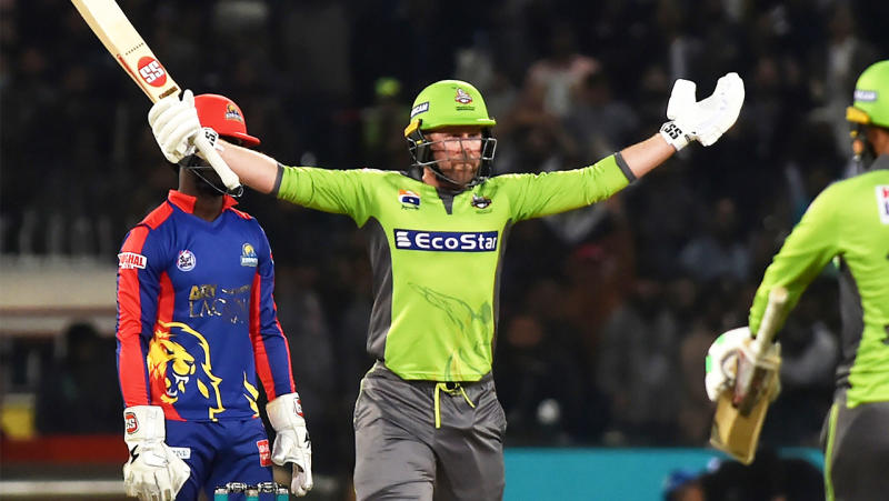Lahore Qalandars's player Ben Dunk lifts his arms and celebrates after hitting the winning runs.