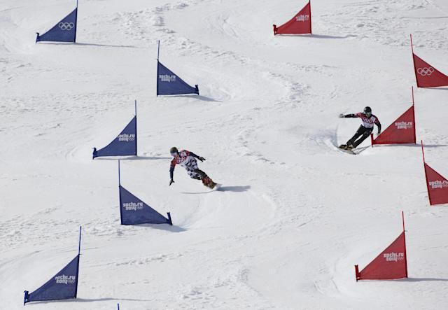 Russia's Vic Wild, left, and Italy's Roland Fischnaller compete in their second run in a snowboard parallel slalom quarterfinal at the Rosa Khutor Extreme Park, at the 2014 Winter Olympics, Saturday, Feb. 22, 2014, in Krasnaya Polyana, Russia. (AP Photo/Andy Wong)