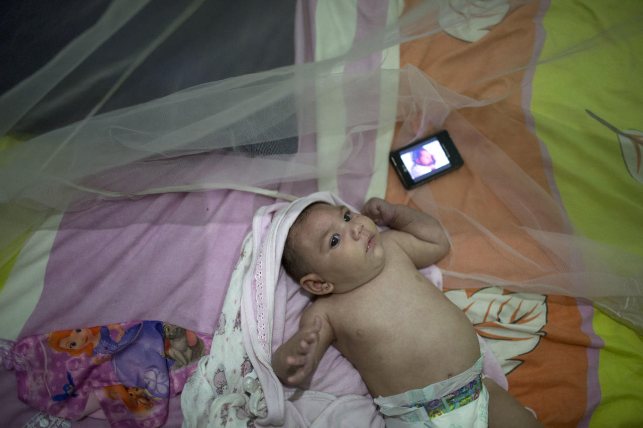 Luiza, who was born with microcephaly, listens to music playing from a mobile phone at her grandmother's house in Santa Cruz do Capibaribe, Pernambuco state, Brazil, Saturday, Feb. 6, 2016. The Zika virus, spread by the Aedes aegypti mosquito, thrives in people's homes and can breed in even a bottle cap's-worth of stagnant water. The virus is suspected to be linked with occurrences of microcephaly in new born babies, but no link has been proven yet. (AP Photo/Felipe Dana)