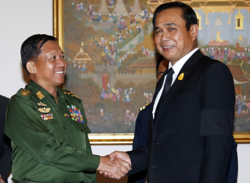 Myanmar's military Chief Senior-General Min Aung Hlaing (L) shakes hands with Thailand's Prime Minister Prayuth Chan-ocha at Government House in Bangkok