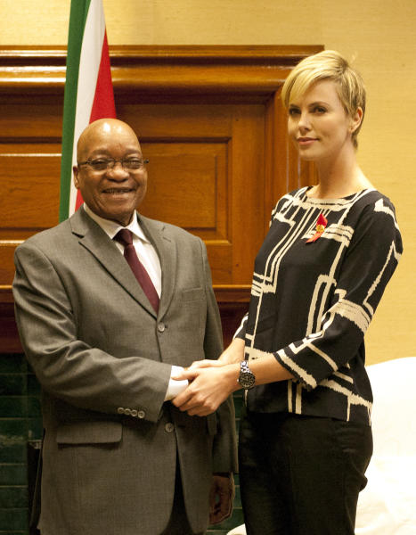 """South African President Jacob Zuma, left, meets South African actress Charlize Theron, right, at his Union Building office in Pretoria, South Africa, Monday, 29 July 2013, ahead of their meeting, to discuss the fight against HIV and Aids, and """"how collaboration can assist mitigate the pandemic's negative impact on young girls"""". (AP Photo/Themba Hadebe)"""