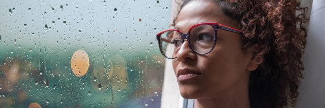 A woman sits alone looking outside a window soaked with rain.