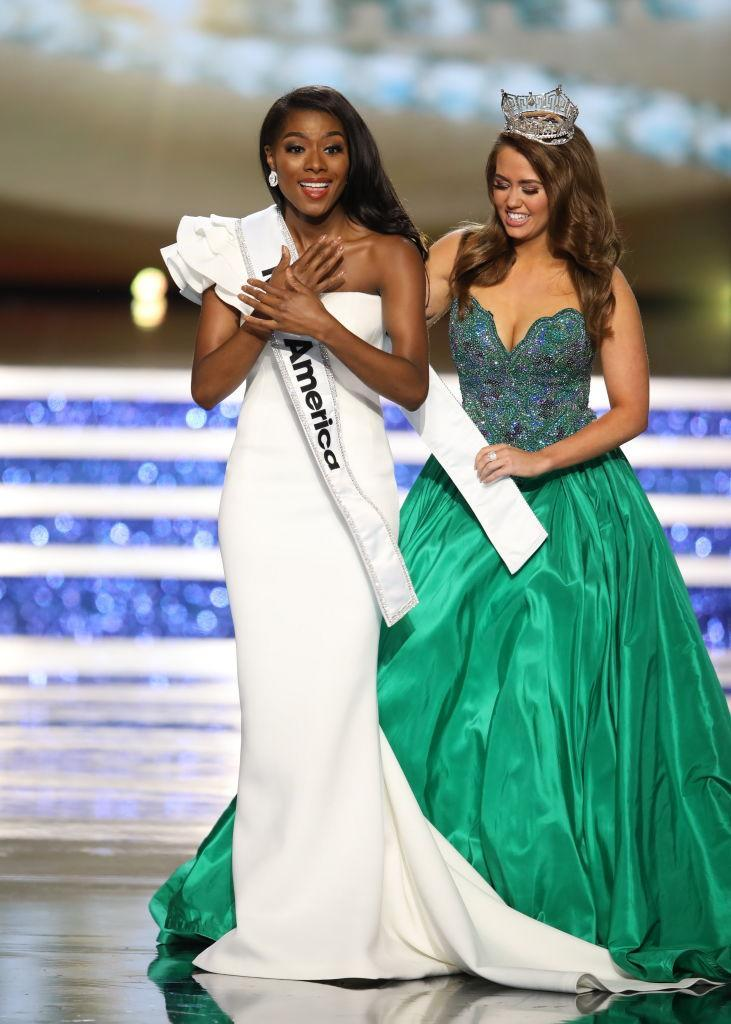 Miss America 2018 Cara Mund, right, helps Miss America 2019, Nia Imani Franklin, with her sash. (Photo: Getty Images)