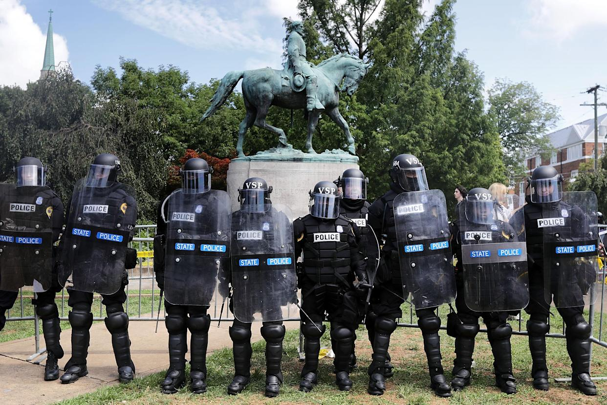 "Virginia State Police in riot gear stand in front of the statue of Gen. Robert E. Lee before forcing white nationalists, neo-Nazis and members of the ""alt-right"" out of Emancipation Park after the ""Unite the Right"" rally was declared an unlawful gathering Aug. 12, 2017, in Charlottesville, Va. (Photo: Chip Somodevilla/Getty Images)"