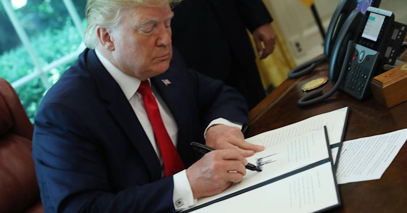 U.S. President Donald Trump signs an executive order imposing new sanctions on Iran, in the Oval Office at the White House on June 24, 2019 in Washington, DC.