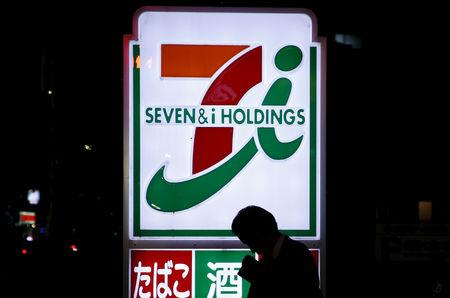 FILE PHOTO: A pedestrian walks in front of a signboard of Seven & I Holdings' 7-Eleven convenience store in Tokyo