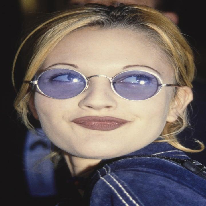 Photo of Drew Barrymore in a brick-colored lipstick and blue sunglasses