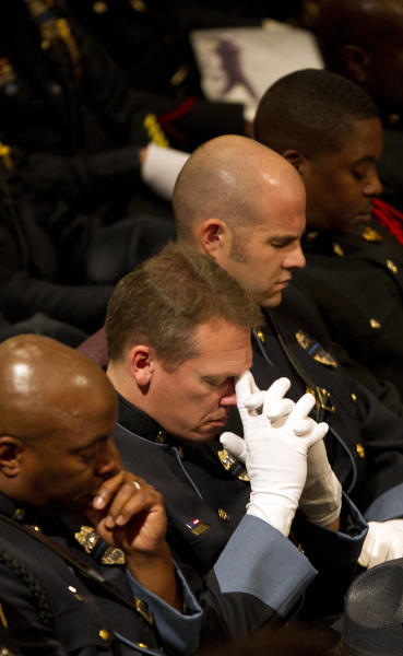 Police officers pray during a memorial service for Atlanta Police helicopter pilot Richard J. Halford Friday, Nov. 9, 2012 in Atlanta. Halford was one of two officers killed last Saturday night in a helicopter crasher while assisting in a search for a missing child. (AP Photo/John Bazemore)