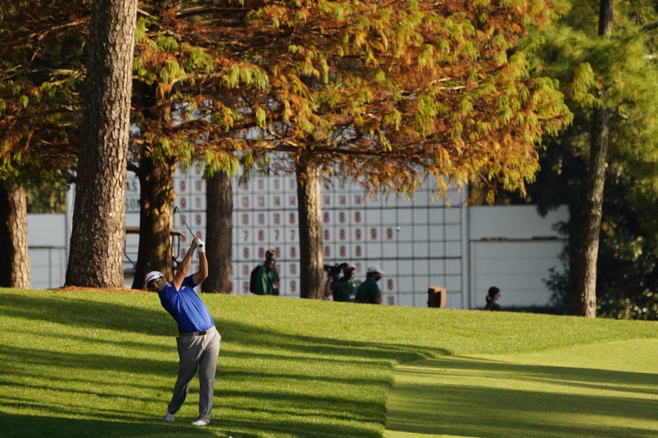 FILE - In this Nov. 14, 2020, file photo, Jon Rahm, of Spain, hits on the 13th hole during the third round of the Masters golf tournament in Augusta, Ga., in this Saturday, Nov. 14, 2020, file photo. Last year the Masters was played in November, amid autumn hues of gold, orange and red in the trees. (AP Photo/Matt Slocum, File)