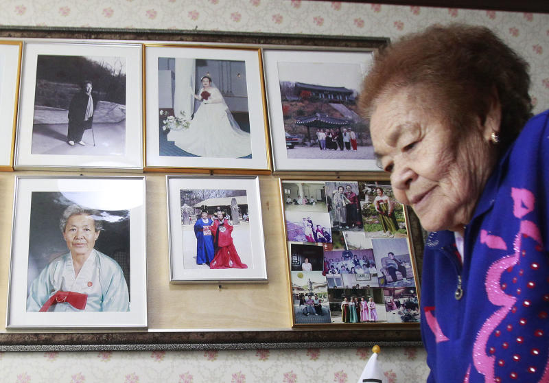 In this Feb. 3. 2014, Kim Gun-ja, 89, former comfort woman who was forced to serve for the Japanese troops as a sex slave during World War II, passes by her wedding picture, top center, at the House of Sharing, a nursing home and museum for 10 former sex slaves, in Toechon, South Korea. There are only 55 women left who registered with the South Korean government as former sex slaves from the war - down from a peak of more than 230. Their average age is 88. (AP Photo/Ahn Young-joon)