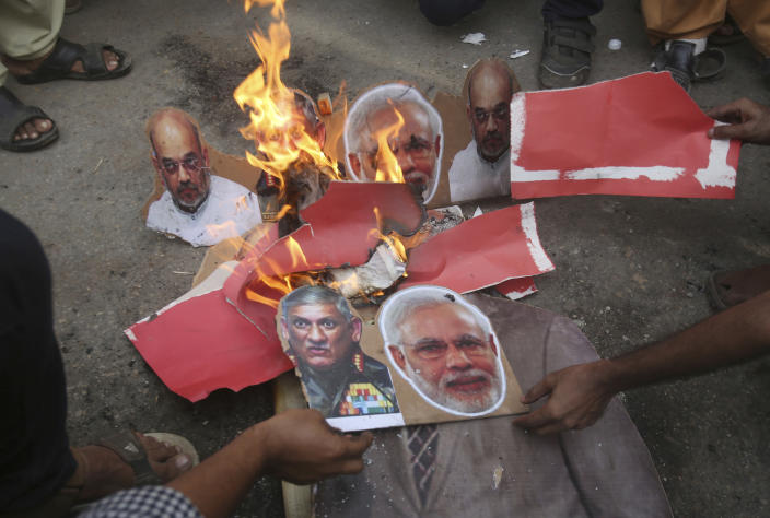 Pakistani protesters burn posters of Indian leaders during a protest in Karachi, Pakistan, Friday, Aug. 9, 2019. Hundreds of activists held peaceful rallies across Pakistan to condemn India and its decisions on Kashmir. (AP Photo/Fareed Khan)