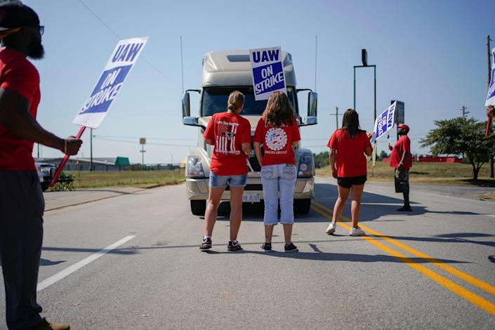 Striking plant workers block the passage of a truck outside the General Motor assembly plant in Bowling Green, Ky, Sept. 16, 2019.