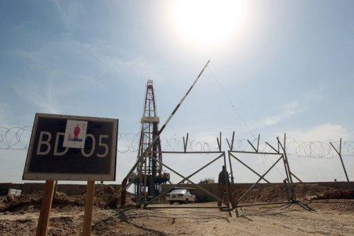 A Gazprom security man walks behind a fence at a drilling platform south of Baghdad, on October 18, 2012