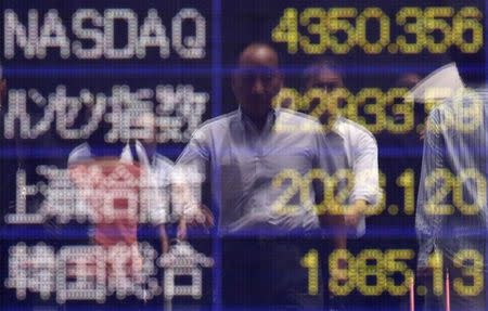 A man is reflected on an electronic board showing market indices outside a brokerage in Tokyo