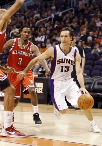 Phoenix Suns guard Steve Nash, right, drives past Milwaukee Bucks guard Brandon Jennings (3) and Drew Gooden, left, on his way to the basket in the third quarter of an NBA basketball game, Sunday, Jan. 8, 2012, in Phoenix. (AP Photo/Paul Connors)