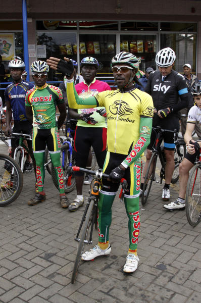David Kinjah speaks to other cyclists before setting off on a group ride in support of Tour de France leader Christopher Froome of Britain, who was born in Kenya, in Nairobi, Kenya, Sunday, July 21, 2013. Froome has two hands firmly on the Tour de France trophy. Only an accident or other freak mishap Sunday on the largely ceremonial final ride to the Champs-Elysees could stop Froome from winning the 100th Tour. (AP Photo/Khalil Senosi)