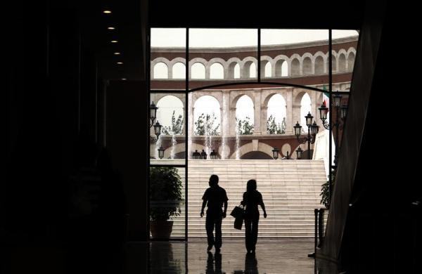 A man and a woman walk through a building that resembles a Roman Coliseum at the Florentia Village in the district of Wuqing, located on the outskirts of the city of Tianjin June 13, 2012.