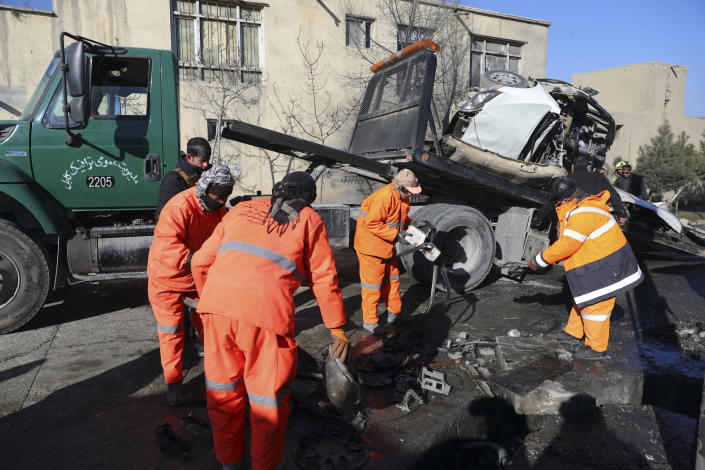 Afghan security personnel and municipality workers remove a damaged vehicle after a roadside bomb attack in Kabul, Afghanistan, Tuesday, Dec. 22, 2020. A roadside bomb tore through a vehicle in the Afghan capital of Kabul Tuesday, killing multiple people, police said. (AP Photo/Rahmat Gul)