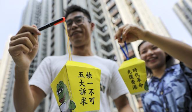 Financial workers hold lanterns outside One Island East in Quarry Bay. Photo: May Tse