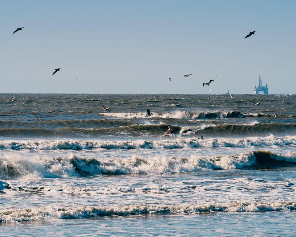 Pelicans fly overhead as a surfer finds a ride between the white wash and an oil rig looms in the background