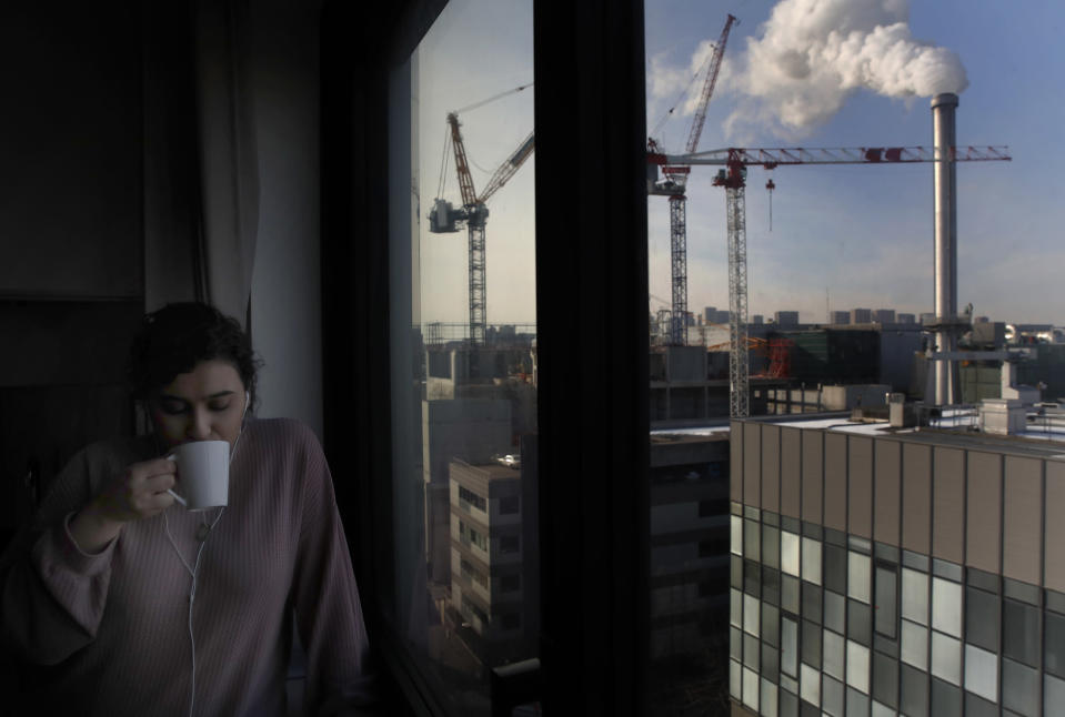Nouhaila Fakhor from Morocco, a student of commerce, drinks a cup of tea in her student housing in Ivry sur Seine, outside Paris, Thursday, Feb. 11, 2021. A quarter of French young professionals can't find work, and many university students are standing in food lines or calling hotlines for psychological help. They are France's future, and their plight is central to the country's battle to emerge from the pandemic. (AP Photo/Christophe Ena)
