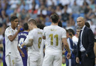 Real Madrid's head coach Zinedine Zidane, right, talks with his player during the Spanish La Liga soccer match between Real Madrid and Valladolid at the Santiago Bernabeu stadium in Madrid, Spain, Saturday, Aug. 24, 2019. (AP Photo/Paul White)