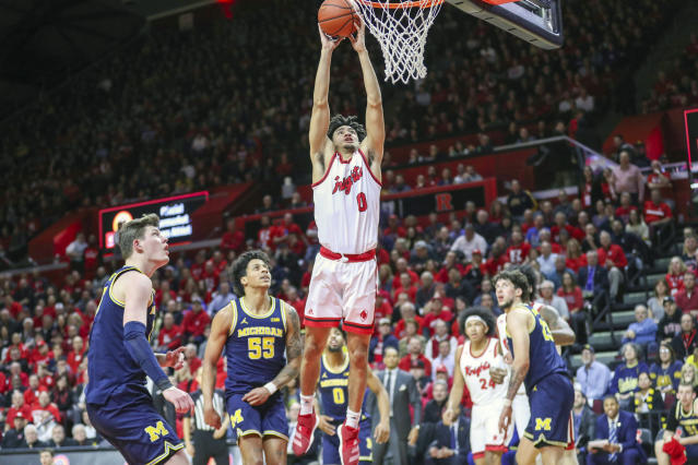 Michigan center Jon Teske, left, and guard Eli Brooks (55) watch as Rutgers guard Geo Baker (0) dunks the ball during the first half of an NCAA college basketball game, Wednesday, Feb. 19, 2020 in Piscataway, N.J. (Andrew Mills/NJ Advance Media via AP)