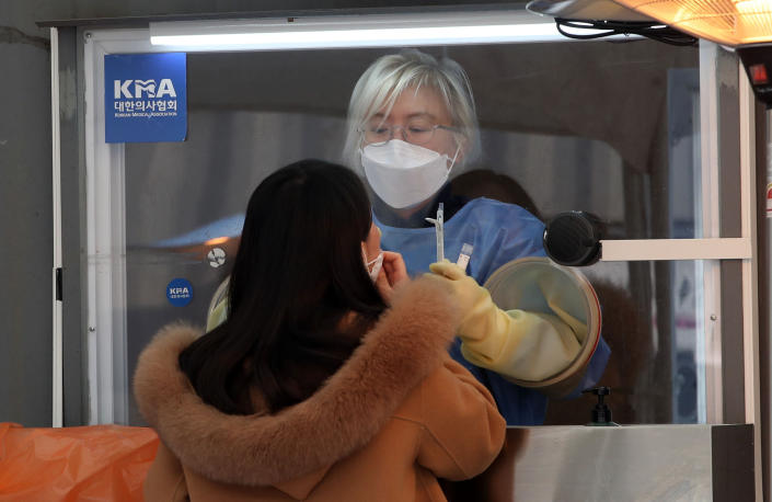 A medical worker wearing protective gears takes sample at a coronavirus testing site in Seoul, South Korea, Monday, Dec. 28, 2020. South Korea has confirmed its first cases of a more contagious variant of COVID-19 that was first identified in the United Kingdom. (Park Ju-sung/Newsis via AP)