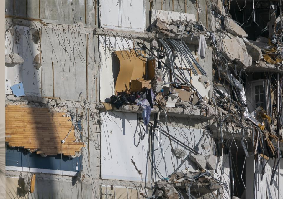 Personal belongings dangle from inside the partially collapsed Champlain Towers South Condo building in Surfside, Fla., on Saturday, July 3, 2021. (Matias J. Ocner/Miami Herald via AP)