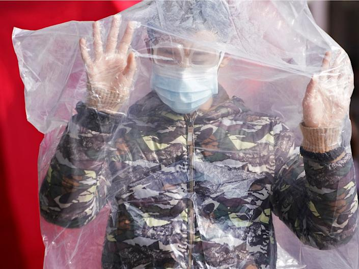 A passengers wearing a mask and covered in a plastic cape in Shanghai.JPG