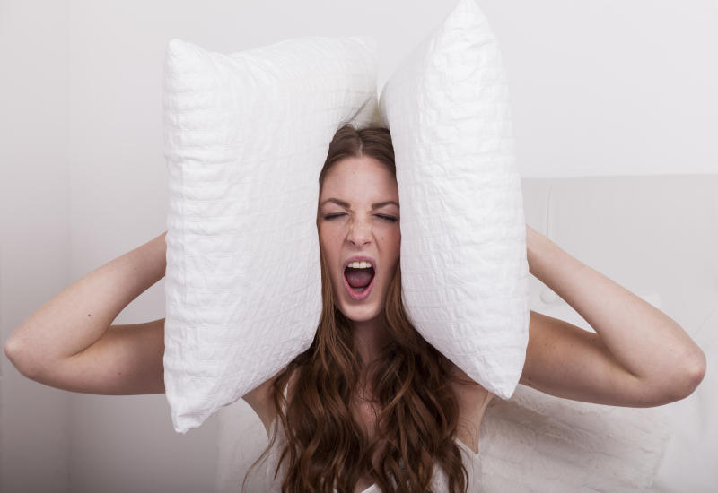 angry woman holds pillows to her ears due to extreme noise of the neighbours
