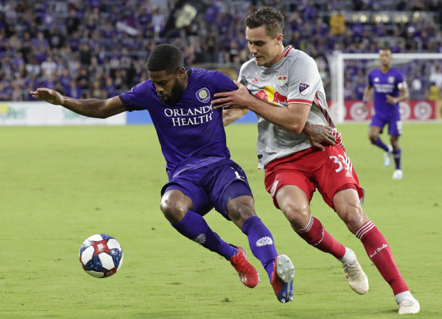 Orlando City's Ruan, left, and New York Red Bulls' Aaron Long (33) battle for possession of the ball during the first half of an MLS soccer match, Sunday, July 21, 2019, in Orlando, Fla. (AP Photo/John Raoux)
