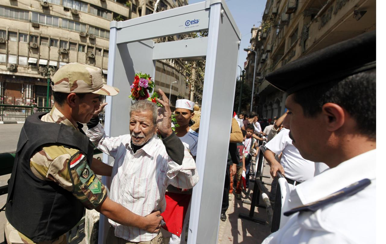 A police officer searches a supporter of Egypt's military after he passed through a metal detector at an entrance to Tahrir square as people gathered to celebrate the anniversary of an attack on Israeli forces during the 1973 war, in Cairo October 6, 2013. REUTERS/Mohamed Abd El Ghany (EGYPT - Tags: POLITICS CIVIL UNREST)