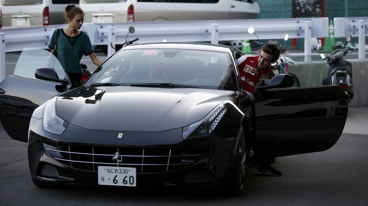 Ferrari Formula One driver Fernando Alonso of Spain and his girlfriend Dasha Kapustina leave after the qualifying session of the Japanese F1 Grand Prix at the Suzuka circuit October 12, 2013. REUTERS/Toru Hanai (JAPAN - Tags: SPORT MOTORSPORT F1 ENTERTAINMENT)