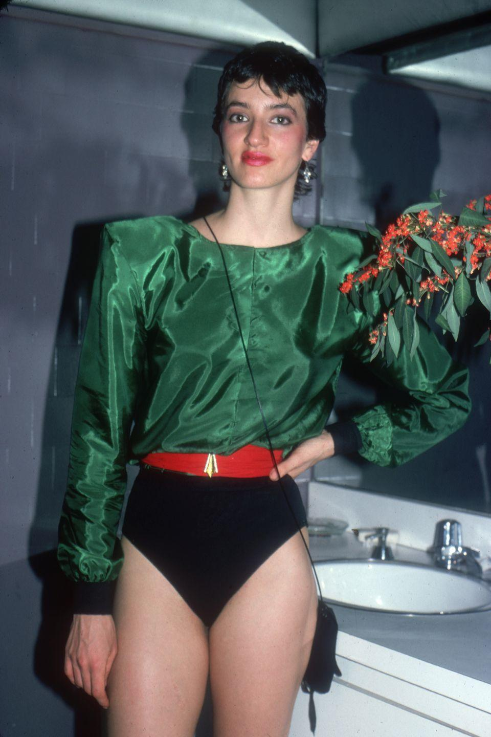 <p>A Studio 54 club-goer wears a green blouse with dramatic shoulder pads over a black leotard. </p>