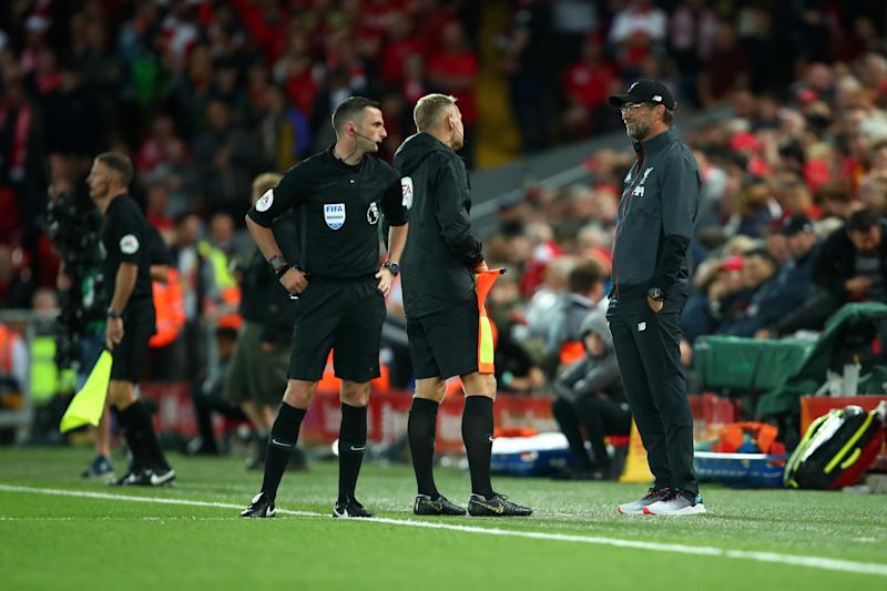 LIVERPOOL, ENGLAND - AUGUST 09: The referee and match officials have issues with their communication head sets before the start of the second half during the Premier League match between Liverpool FC and Norwich City at Anfield on August 9, 2019 in Liverpool, United Kingdom. (Photo by Robbie Jay Barratt - AMA/Getty Images)