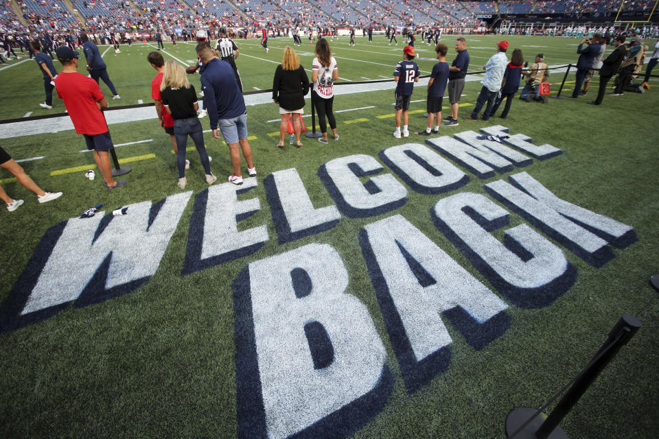Welcome Back appears in paint on the sidelines as fans watch the New Englands Patriots warm up prior to an NFL football game against the Miami Dolphins, Sunday, Sept. 12, 2021, in Foxborough, Mass. (AP Photo/Stew Milne)