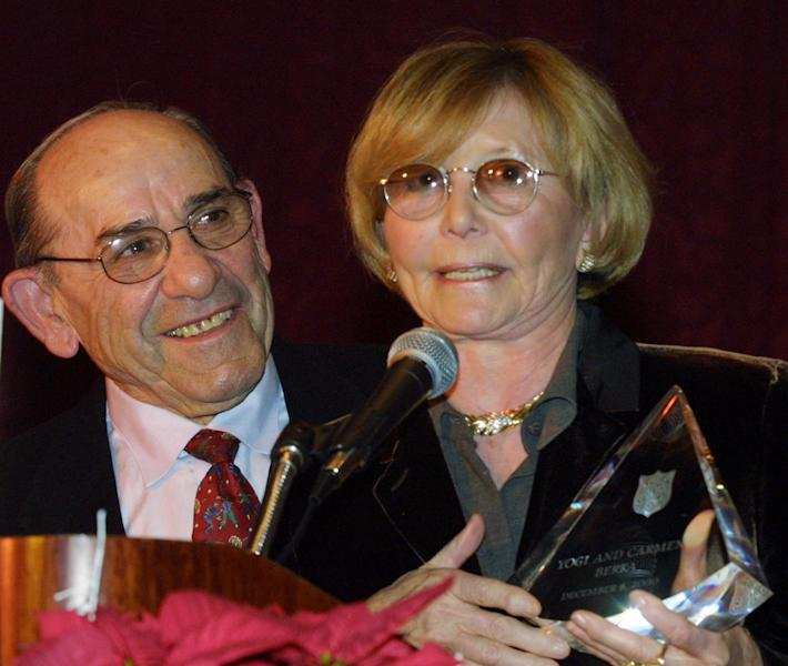 """FILE- In this Dec. 6, 2000 file photo, Baseball Hall-of-Famer Yogi Berra listens as his wife Carmen accepts the """"Pinnacle of Achievement"""" award at the Salvation Army Association of Greater New York's Annual Luncheon in New York. According to NJ.com, Dave Kaplan, the director of the Yogi Berra Museum and Learning Center, said that Carmen Berra died of complications from a stroke on Thursday, March 6, 2014. She was 85. (AP Photo/Shawn Baldwin, File)"""