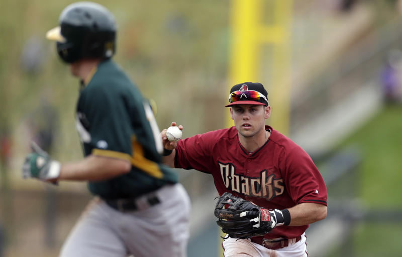 Arizona Diamondbacks shortstop Chris Owings, right, chases pinch runner Oakland Athletics' Billy Burns who is caught stealing second base during the sixth inning of an exhibition spring training baseball game on Thursday, March 6, 2014, in Scottsdale, Ariz. (AP Photo/Gregory Bull)