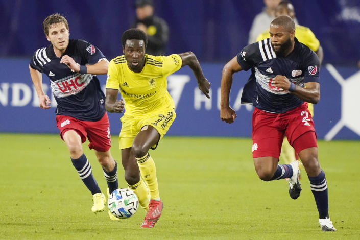 Nashville SC forward Abu Danladi (7) dribbles the ball ahead of New England Revolution's Scott Caldwell, left, and Andrew Farrell, right, during the first half of an MLS soccer match Friday, Oct. 23, 2020, in Nashville, Tenn. (AP Photo/Mark Humphrey)