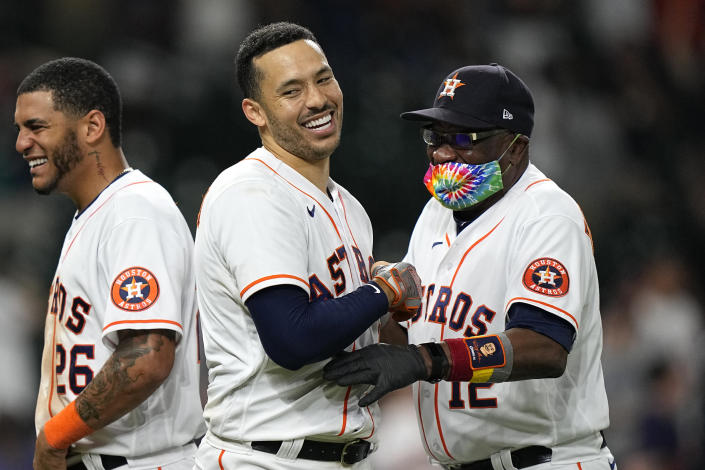 Houston Astros' Carlos Correa, center, celebrates with manager Dusty Baker Jr. (12) after hitting a game-winning RBI ground-rule double against the Seattle Mariners during the 10th inning of a baseball game Tuesday, Sept. 7, 2021, in Houston. The Astros won 5-4 in 10 innings. (AP Photo/David J. Phillip)