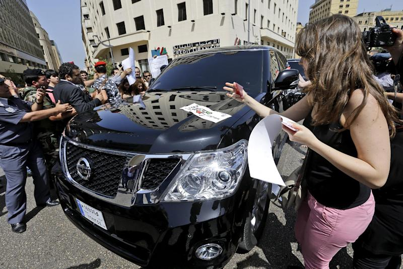 In this picture taken on May 31, 2013, a Lebanese pro-democracy protester, right, pastes an anti-parliament sticker on the car of a Lebanese lawmaker during a protest against the 17 months extension of the Lebanese parliament, near the parliament building in Beirut, Lebanon. Lebanese lawmakers meet in the Lebanese Parliament during a session to debate whether to extend their term 17 months, in Beirut, Lebanon. Since the current parliament was elected in June 2009, the lawmakers have met 21 times to pass 169 laws, mostly related to raise government and civil servants' salaries, receive foreign aid and amend election law that will enable their re-election. In 2013, Lebanon's lawmakers only met twice to pass two laws, one of which was to extended their mandate for 18 months. (AP Photo/Hussein Malla)