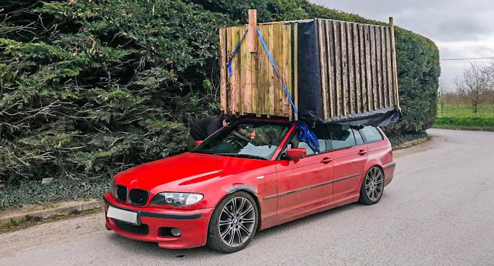 A red BMW with a shed strapped to its roof from a front-on angle.