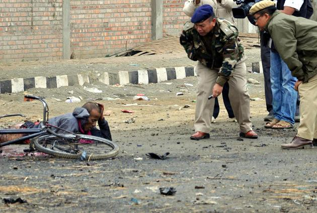 Indian police personnel (R) talk to an injured person at the bomb blast site in Imphal, India's northeastern state capital of Manipur on November 30, 2011. A bomb in the northeastern Indian state of Manipur killed a man suspected of planting the explosives, police said, days ahead of a visit by the prime minister. AFP PHOTO/STR