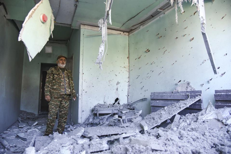 A man wearing a military uniform stands inside a house destroyed by shelling during a military conflict in Stepanakert in the separatist region of Nagorno-Karabakh, Saturday, Oct. 17, 2020. Stepanakert, the regional capital of Nagorno-Karabakh, came under intense shelling overnight, leaving three civilians wounded, according to separatist authorities. (David Ghahramanyan, NKR InfoCenter/PAN Photo via AP)