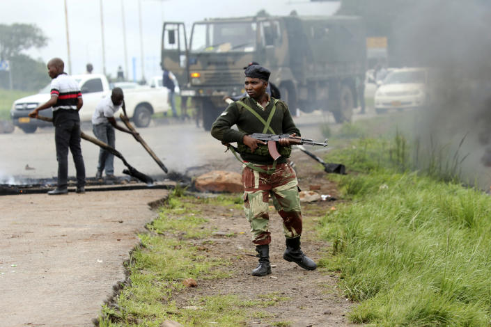 A soldier patrols as a barricade is removed during a demonstration over the hike in fuel prices in Harare, Zimbabwe, Tuesday, Jan. 15, 2019. A Zimbabwean military helicopter on Tuesday fired tear gas at demonstrators blocking a road and burning tires in the capital on a second day of deadly protests after the government more than doubled the price of fuel in the economically shattered country. (AP Photo/Tsvangirayi Mukwazhi)
